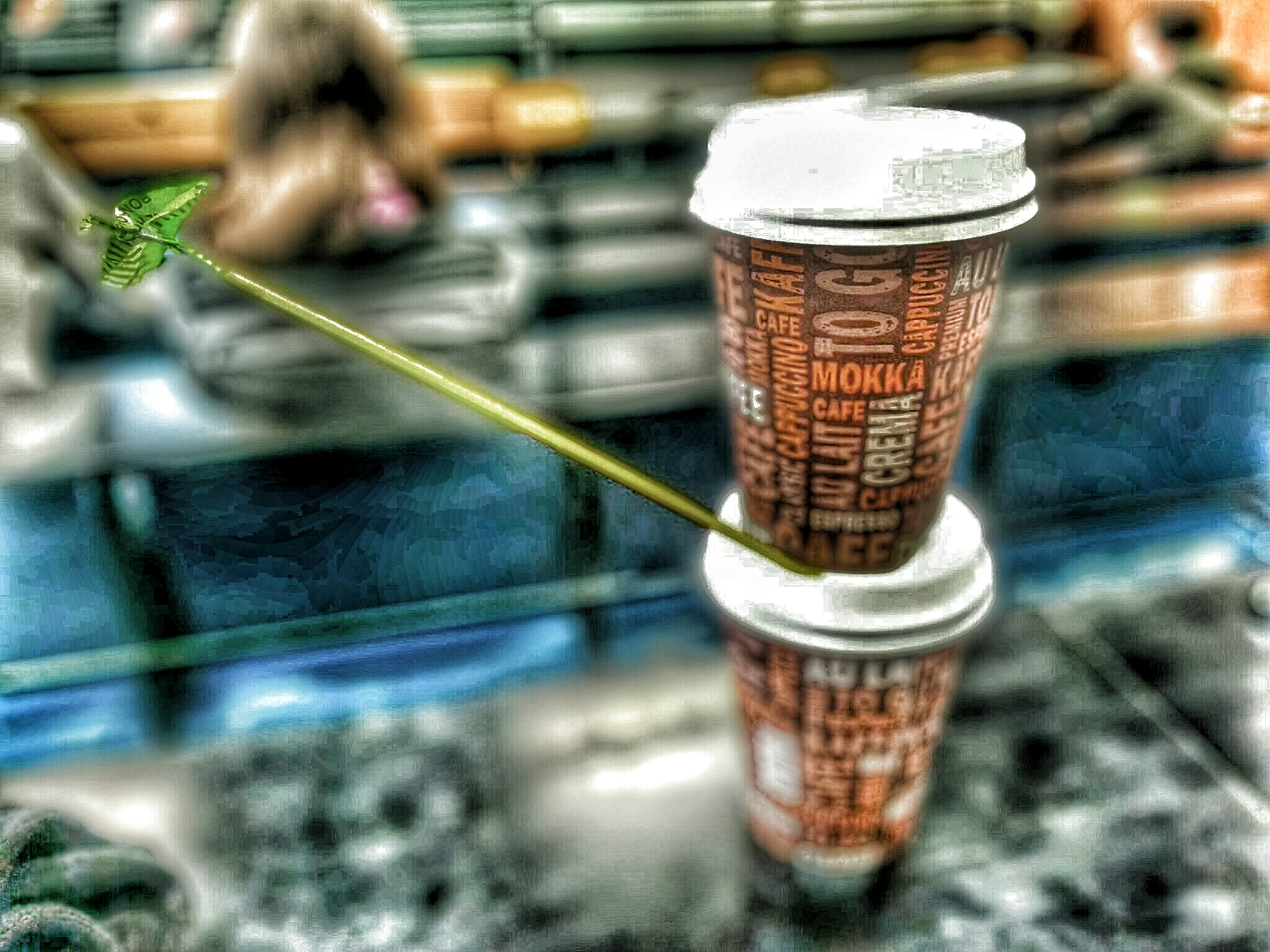 Artistic image of two paper coffee cups stacked on top of each other and a green bird made from bonbon wrapping paper flying away