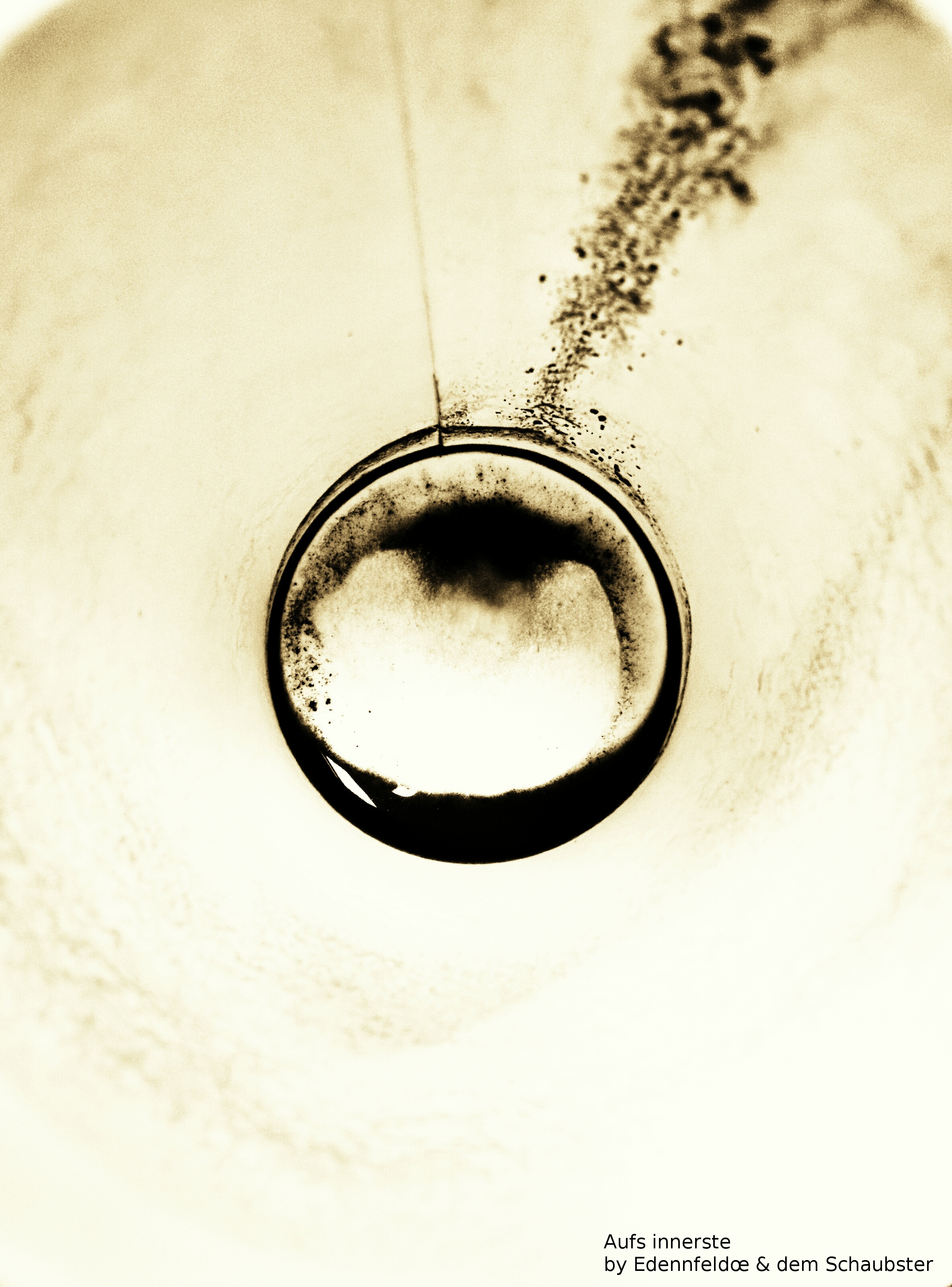 Artistic top down view into a paper coffee cup with black coffee stains at the bottom