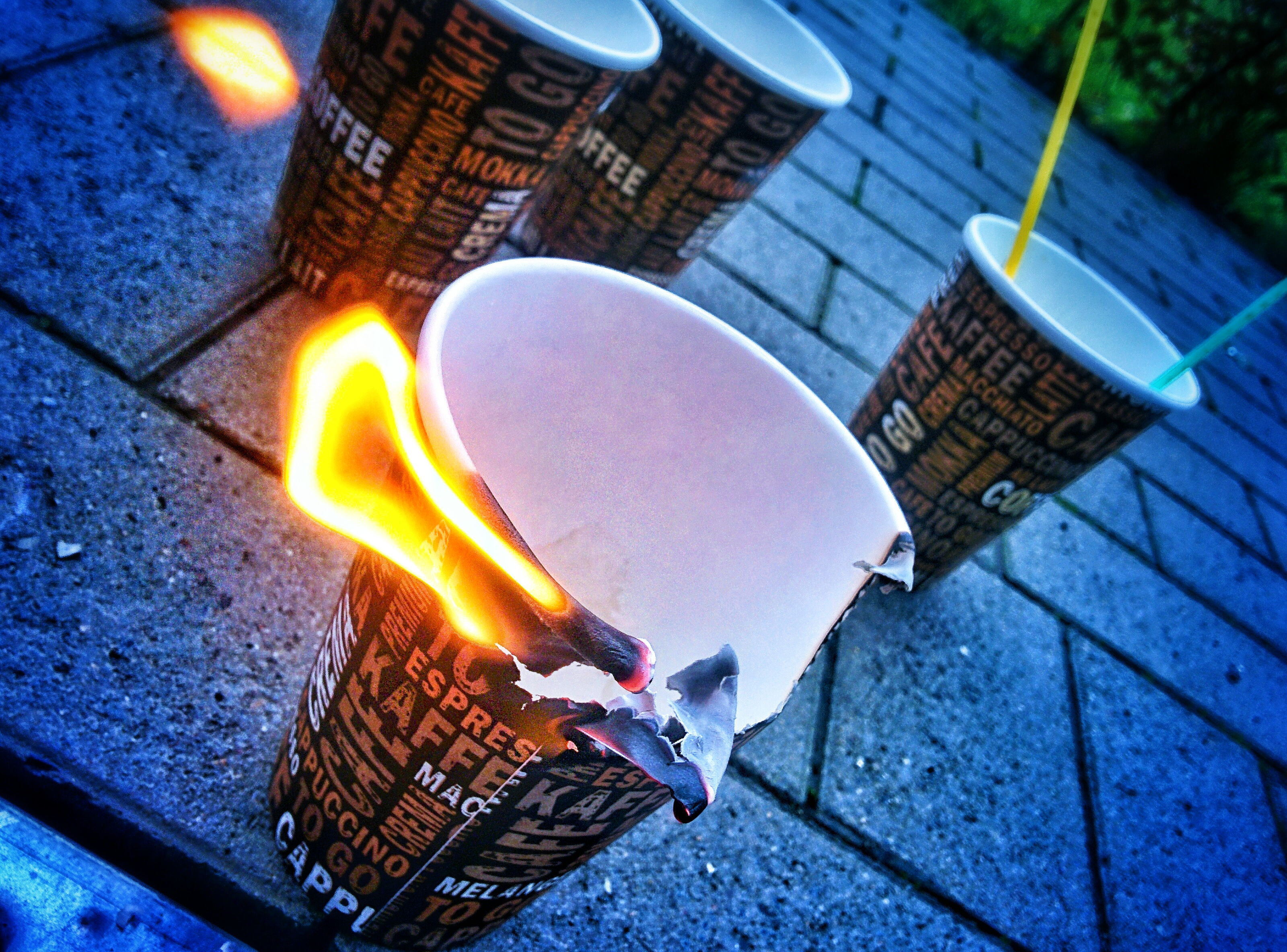 4 paper coffee cups are standing on some paving blocks. The one infront is separated from the others and is on fire.