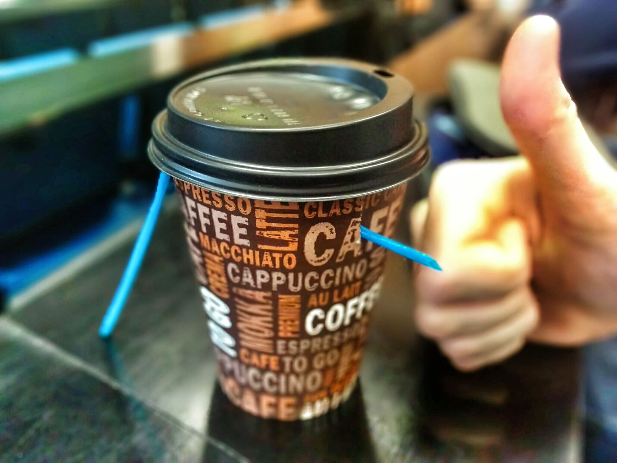 Artistic image of a paper coffee mug and a hand showing a thumbs up. The coffee cup is pierced by a plastic straw.