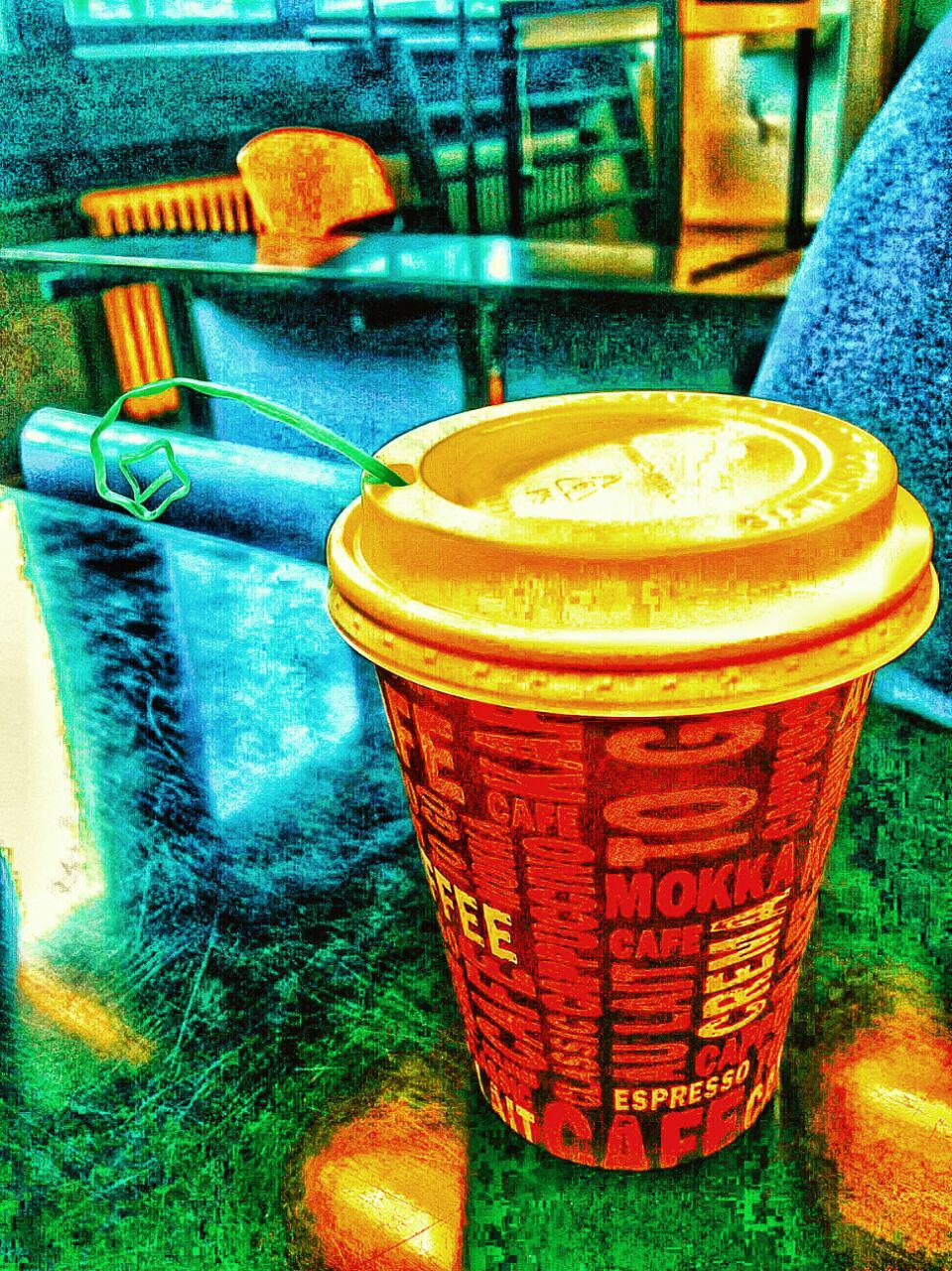 Artistic image of a paper coffee mug with a star coming out of the cap. The straw is curled into a spiral, which gives it the look of an insects antenna.