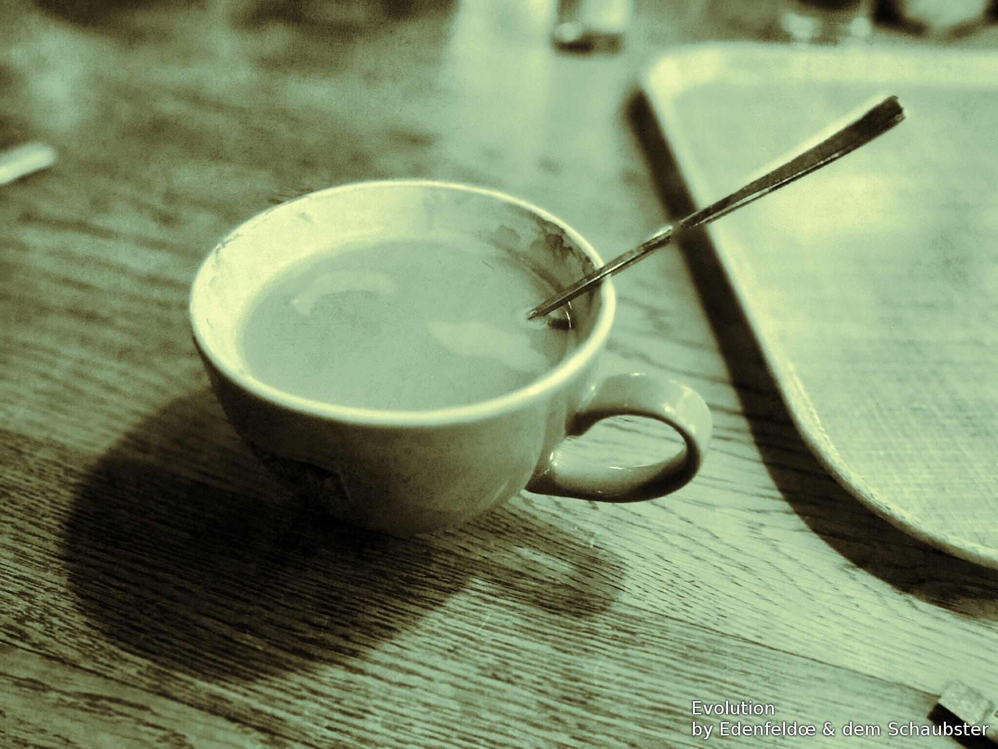 Image of a ceramic coffee mug with a metal spoon in it.