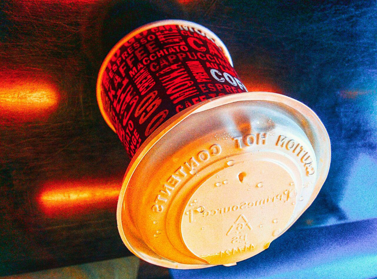 Image of a paper coffee mug with an inverted lid. The image appears to be upside down.