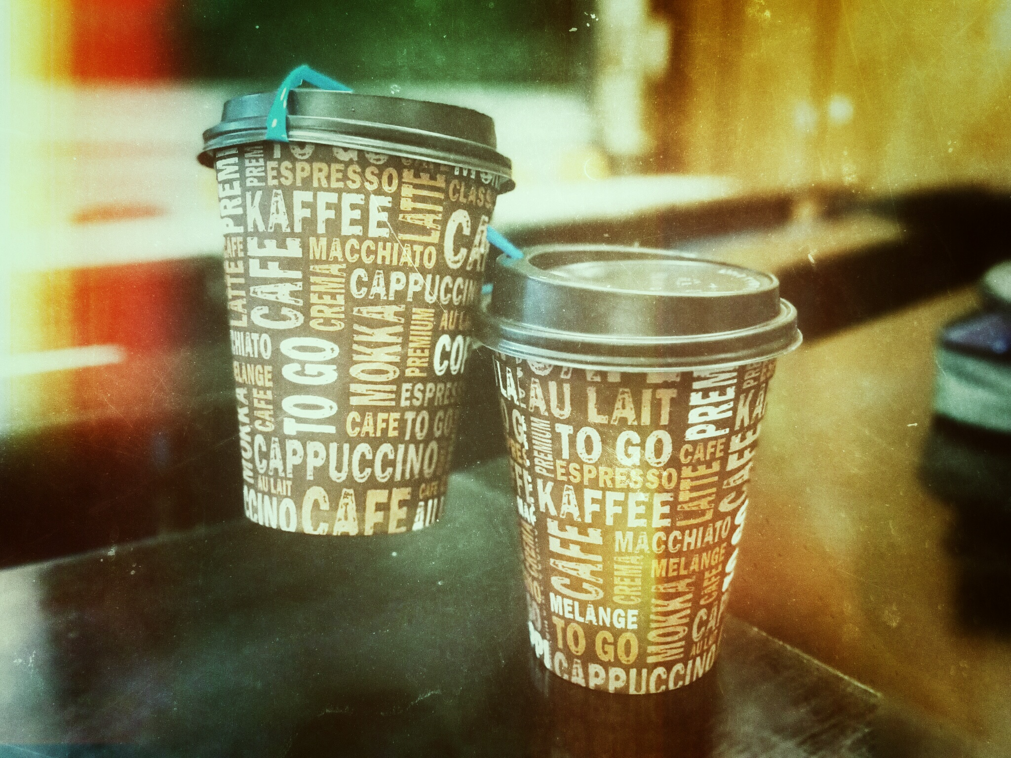 Artistic image of two paper coffee mugs. One of them is lifted above the other with help of a blue straw.