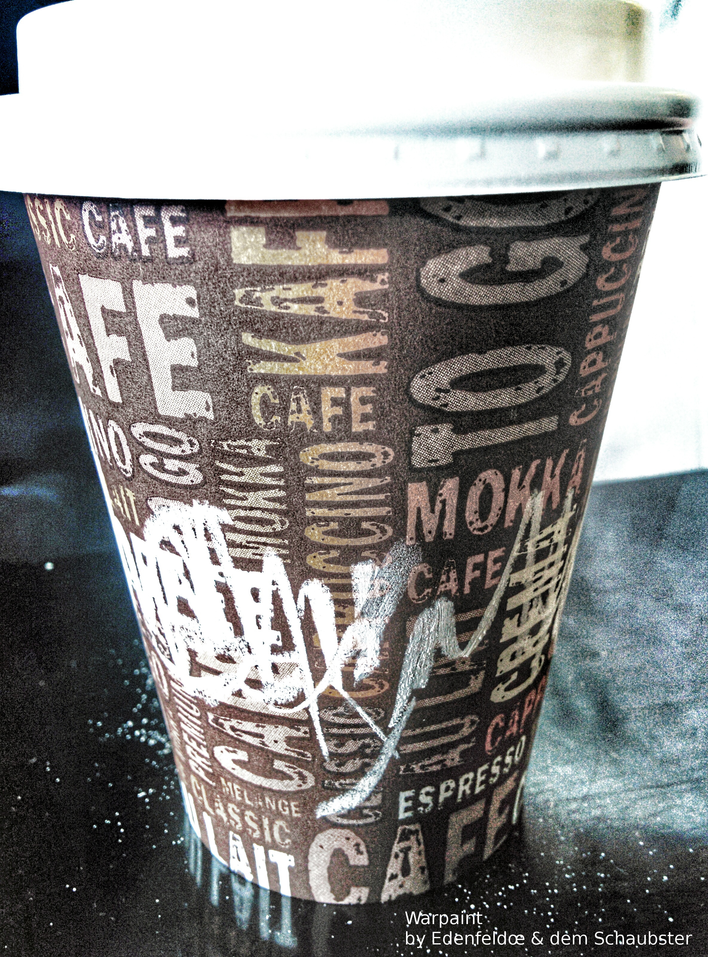 Image of a paper coffee mug with chalk markings on its side.