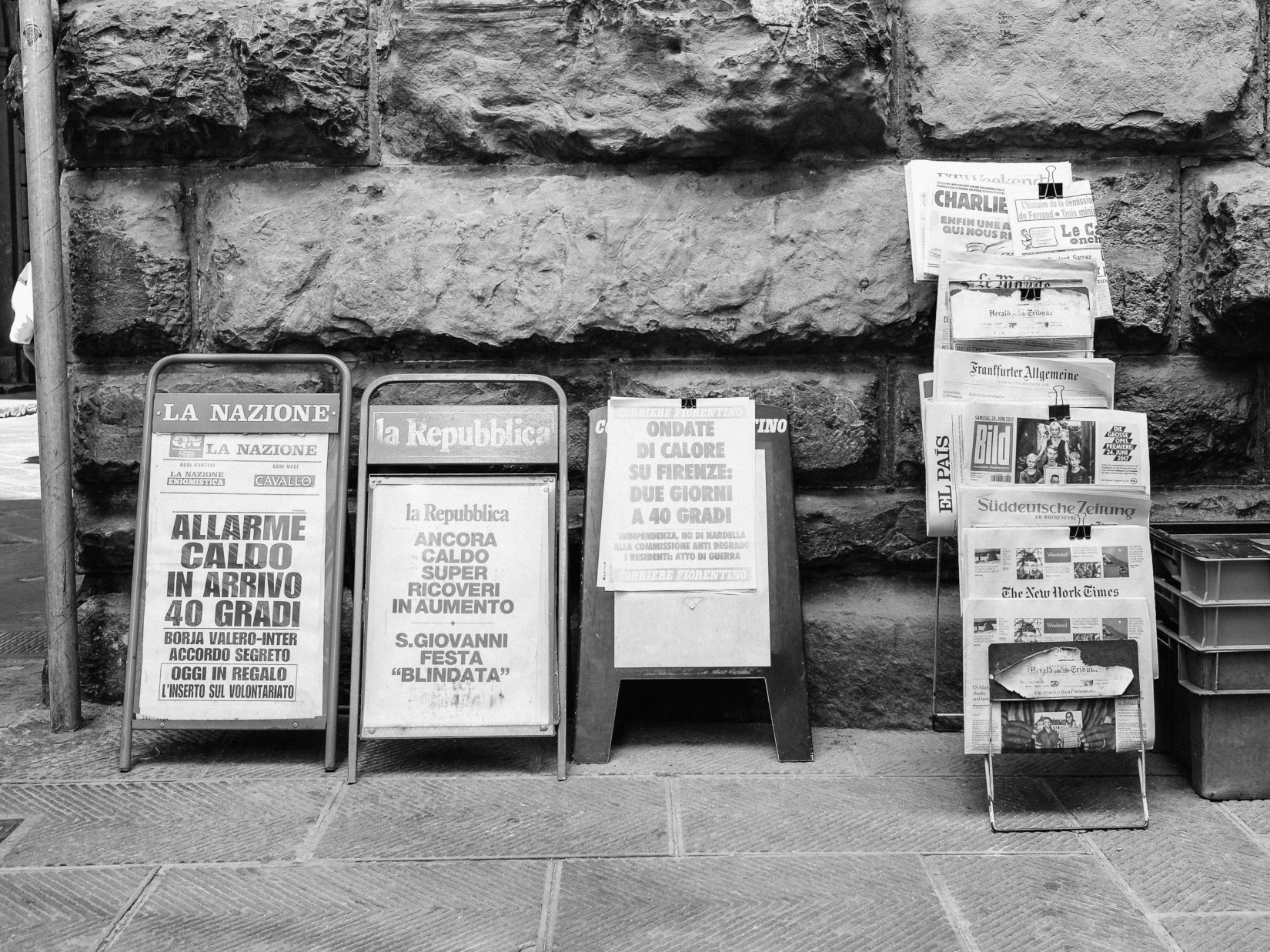 Greyscale image of newspapers on a stand.